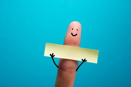 Funny finger holding blank bunner and smiling.