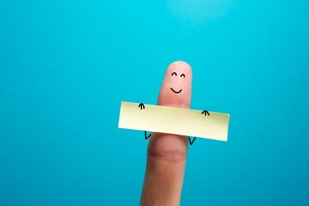 dedo divertido que sostiene bunner en blanco y sonriente.