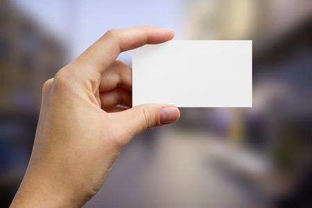 terra arrendada: Mãos segurando um cartão de visita de negócios branco, presente, bilhete, passagem, presente close-up no fundo azul borrado. cópia espaço
