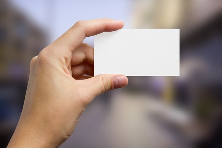 Mains tenant une carte de visite d'affaires blanc, cadeau, billet, passe, présent gros plan sur fond bleu flou. Espace copie Banque d'images