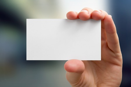 Hands holding a white business visit card, gift, ticket, pass, present close up on blurred blue background. Copy space