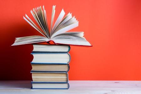 Composición con los viejos libros de tapa dura de la vendimia, Diario, abanicó páginas en la mesa cubierta de madera y fondo rojo. Libros de apilamiento. Volver a la escuela. Espacio en blanco. Antecedentes educacionales.