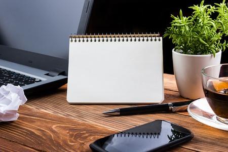 メモ帳、コンピューターとコーヒー カップでのオフィスのテーブル。ビジネス創造的な概念。