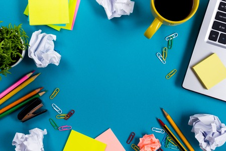 Office table desk with set of colorful supplies, white blank note pad, cup, pen, pc, crumpled paper, flower on blue background. Top view and copy space for text. Foto de archivo
