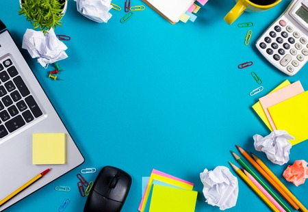 Office table desk with set of colorful supplies, white blank note pad, cup, pen, pc, crumpled paper, flower on blue background. Top view and copy space for text. Stockfoto