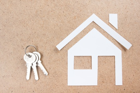 key: Silver key with house figure and on wooden background. Real Estate Concept. Top view