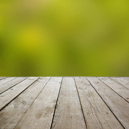 advertising material: Wooden perspective floor with planks on blurred natural summer background, can use for display or montage your products template. Green forest with ray of light and bokeh. Copy space