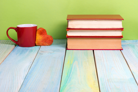 hardback: Colorful composition with vintage old hardback books, diary on wooden deck table and green background. Books stacking. Back to school. Copy Space. Education background Stock Photo