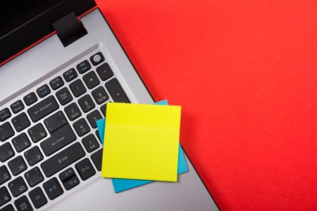 Office table desk with set of colorful supplies, white blank note pad, cup, pen, pc, crumpled paper, flower on red background. Top view and copy space for text.