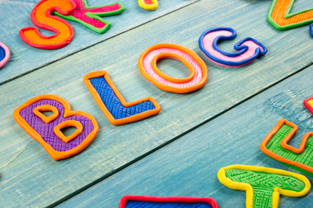 BLOG: Word BLOG made with plasticine letters on old wooden blue board background