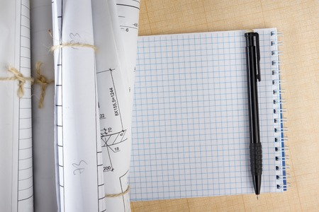 surveying: Architectural blueprints and blueprint rolls on white background