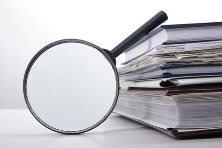 虫眼鏡で書籍のスタック。検索情報 写真素材