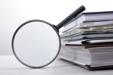 Stack of books with magnifying glass. Search information