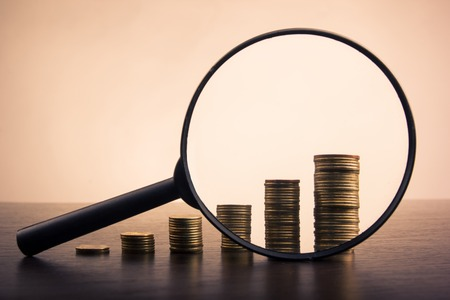 虫眼鏡、チェス本と緑色の背景上のコインの黄金の列です。領域をコピーします。銀行。銀行に行く