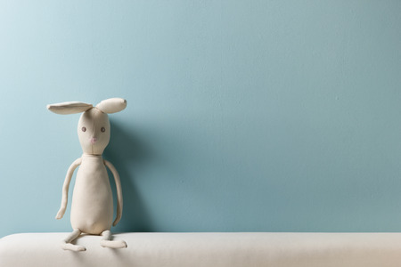 Home interior. Childhood. Blue background. Toy sitting on a couch. Copy space