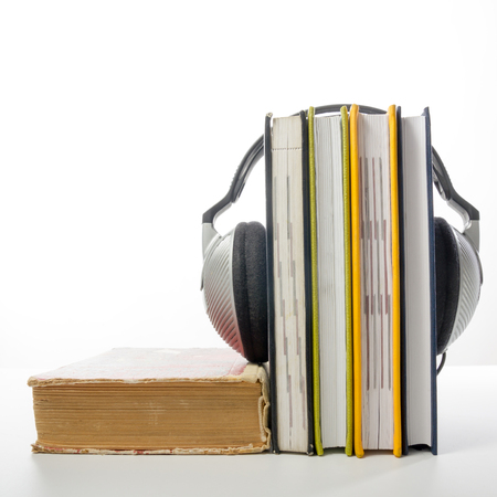 audio book: Audio book Stack of hardback books and electronic reader. Electronic library concept. Back to school. Copy space.