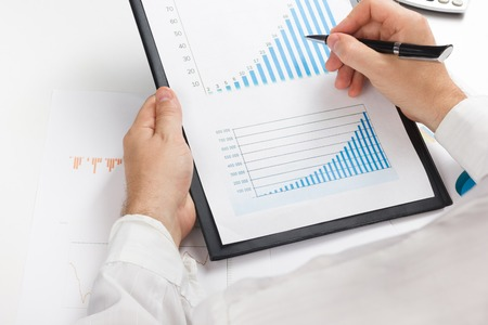 office workers: Businessman counting losses and profit working with statistics, analyzing financial the results on white background. Copy space. Stock Photo