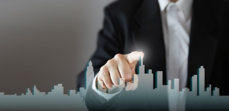 activate: Businessman Activate Growth Process, choosing house, real estate city concept. Skyline Hand pressing the house icon on virtual screen. Business, technology, internet and networking concept. Copy space. Stock Photo