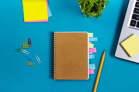 Office table desk with set of colorful supplies, white blank note pad, cup, pen, pc, crumpled paper, flower on blue background. Top view and copy space for text. Фото со стока