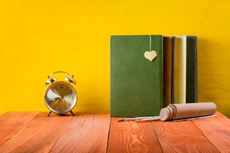 hardback: Colorful composition with vintage old hardback books, diary on wooden deck table and yellow background. Books stacking. Back to school. Copy Space. Education background Stock Photo