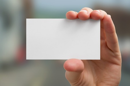 business cards: Hand holding white business card on blurred background. Stock Photo