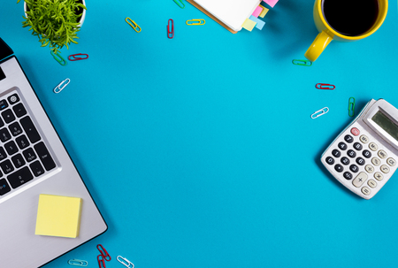 Office table desk with set of colorful supplies, white blank note pad, cup, pen, pc, crumpled paper, flower on blue background. Top view and copy space for text. Standard-Bild