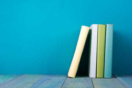 estanterias: Fila de libros, fondo azul sucio, copia espacio libre de la vendimia viejos libros de tapa dura en el estante de madera sobre la mesa cubierta, sin etiquetas, la columna en blanco. De vuelta a la escuela. Antecedentes educacionales