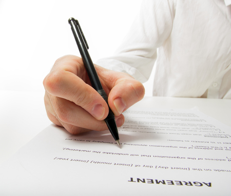 financial official: Businessmans hand signing papers. Lawyer, realtor, businessman sign documents on white background. Copy space for text