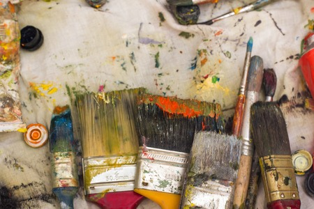 teaching material: Abstract painted canvas. Oil paints on a palette. Colorful background.