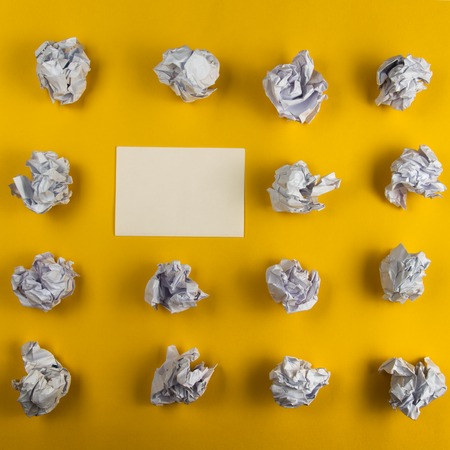 crinkly: Crumpled paper balls and blank sheet of paper with pencil on yellow background. Paper wad. Creativity problems. Searching ideas