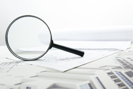 Architectural blueprints, blueprint rolls and magnifying glass on white background