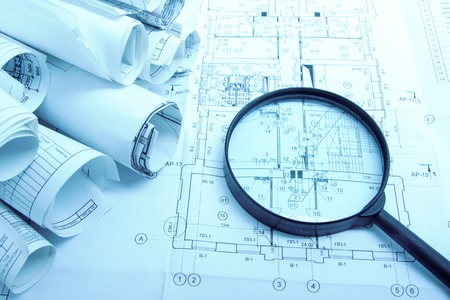 settlement: Architectural blueprints, blueprint rolls and magnifying glass on white background. Toned picture Stock Photo