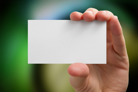 hand with card: Hand holding white business card on blurred background. Stock Photo