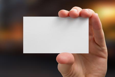 Hand gospodarstwa białego wizytówki na tle rozmazany.