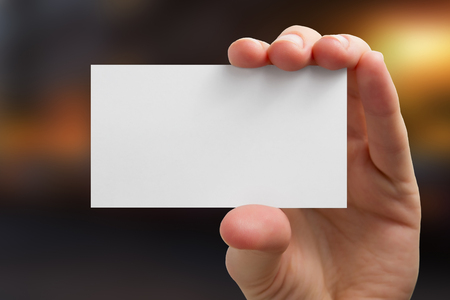 Hand holding white business card on blurred background.