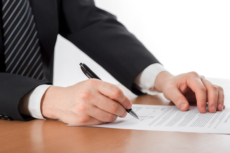 law suit: Businessmans hand signing papers. Lawyer, realtor, businessman sign documents on white background. Copy space for text