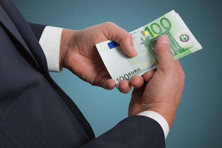 counting money: Businessmans hands counting money euro banknotes in the pocket.