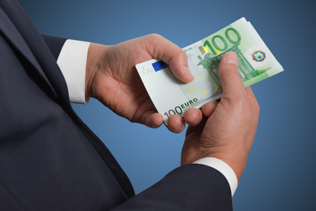 money in the pocket: las manos del hombre de negocios contar dinero de billetes de euro en el bolsillo.