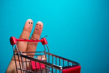 Funny fingers shopping at supermarket with red trolley on blue background. Standard-Bild