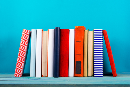 hardback: Stack of colorful books, grungy blue background, free copy space Vintage old hardback books on wooden shelf on the deck table, no labels, blank spine. Back to school. Education background