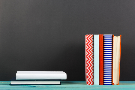 hardback: Composition with old vintage colorful hardback books, diary on wooden deck table and black board background. Books stacking. Back to school. Copy Space. Education background
