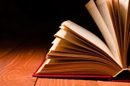 Altes Buch geöffnet in der Bibliothek auf hölzernen Regal. Bildung Hintergrund mit Kopie Platz für Text. Schatten dunklen Hintergrund.