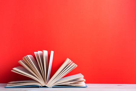 Composition avec de vieux livres cartonnés cru, journal, pages sur la table de terrasse en bois et fond rouge éventé. Livres d'empilage. Retour à l'école. Espace texte. Education fond.