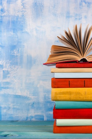 Composition with old vintage colorful hardback books, diary on wooden deck table and artistic blue background. Books stacking. Back to school. Copy Space. Education background Stock Photo