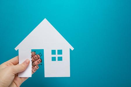 Hand mit lustigen Finger hält weißes Papier Haus Abbildung auf blauem Hintergrund. Immobilien-Konzept. Ökologisches Bauen. Kopieren Sie Platz Ansicht von oben