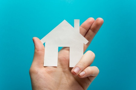Hand holding white paper house figure on blue background. Real Estate Concept. Ecological building. Copy space top view Stock Photo