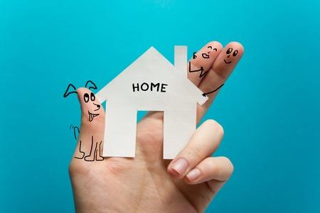 ホーム。ブルーの背景にホワイト ペーパー家図を持っている手。不動産の概念。生態学的な建物。コピー スペース平面図