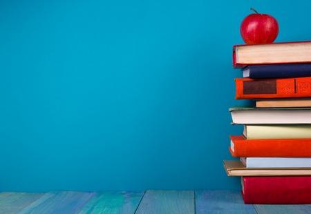 libros viejos: Pila de libros de colores, fondo azul sucio, copia espacio libre de la vendimia viejos libros de tapa dura en el estante de madera sobre la mesa cubierta, sin etiquetas, la columna en blanco. De vuelta a la escuela. Antecedentes educacionales