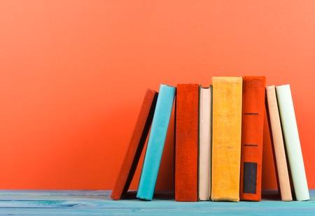ヴィンテージの古いハードカバーの本と組成日記、ウッドデッキのテーブルと赤の背景に煽らページ。スタッキングの本。学校に戻る領域をコピー 写真素材