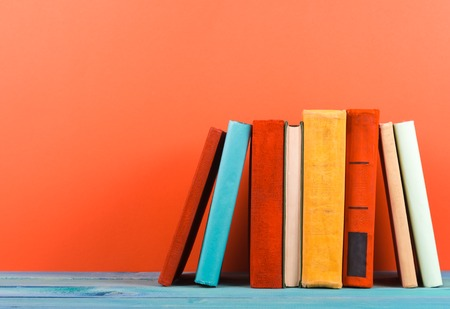 copy space: Composition with vintage old hardback books, diary, fanned pages on wooden deck table and red background. Books stacking. Back to school. Copy Space. Education background.